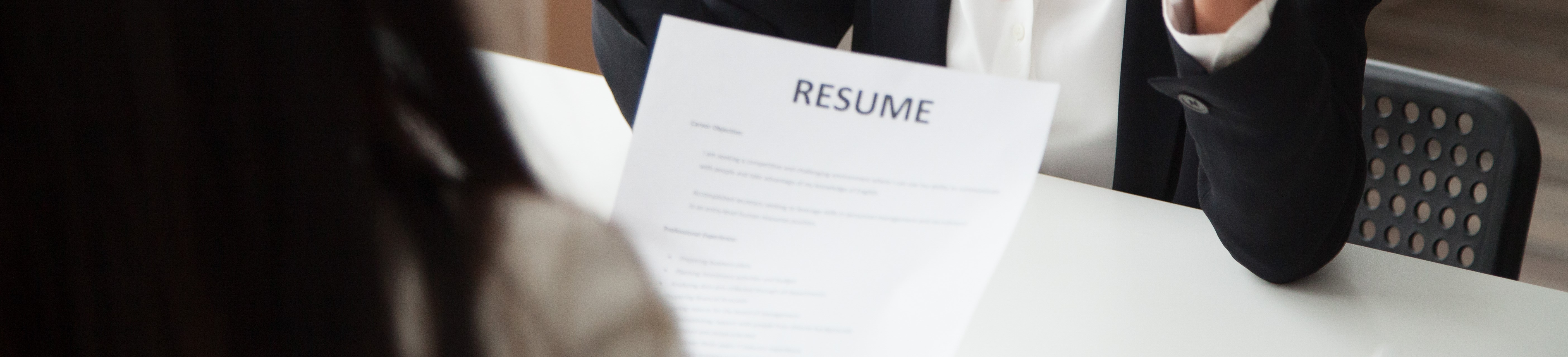 Job interview with two women and one holding resume