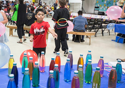 Boy doing carnival-type ring toss game at indoor celebration