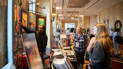 Exhibitor pointing to painting and speaking to conference attendees